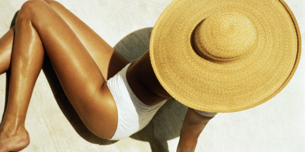 Beautiful tanned woman in white bathing suit wearing a huge sun hat